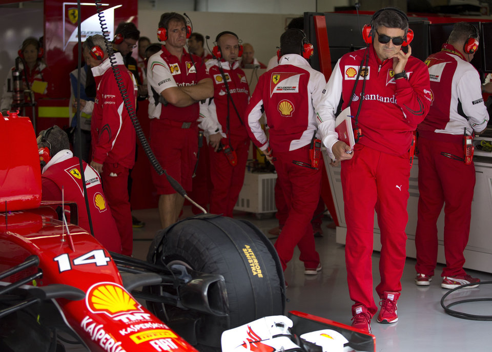 Photo - Ferrari's new team principal, Marco Mattiacci,  second right, stands at the team garage during the practice session ahead of Sunday's Chinese Formula One Grand Prix at Shanghai International Circuit in Shanghai, China Friday, April 18, 2014. (AP Photo/Andy Wong)