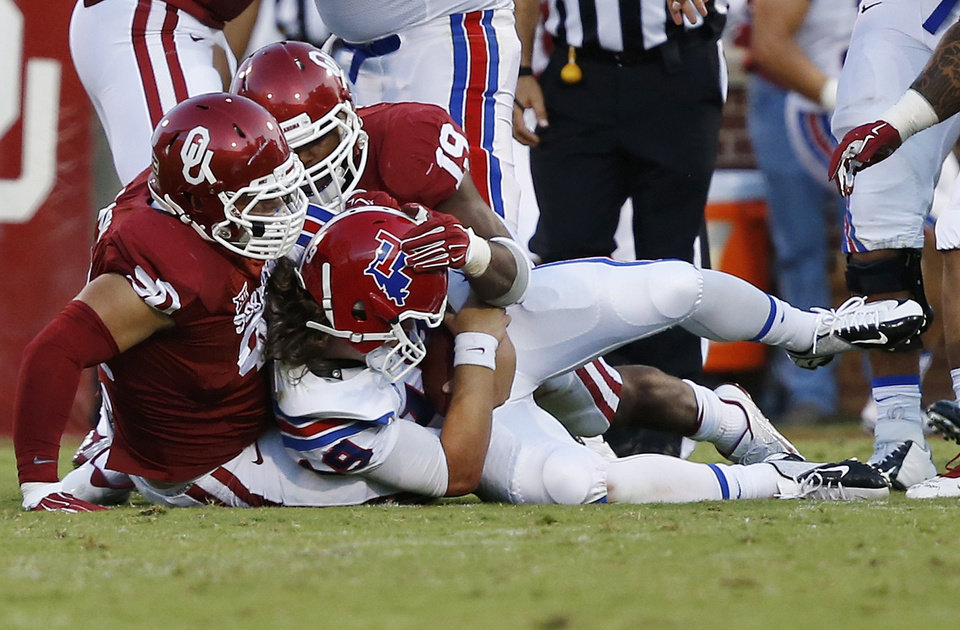 Photo - Louisiana Tech quarterback Cody Sokol (19) is sacked by Oklahoma defensive end Matt Dimon (90) and linebacker Eric Striker (19) in the second quarter of an NCAA college football game in Norman, Okla., Saturday, Aug. 30, 2014. (AP Photo/Sue Ogrocki)