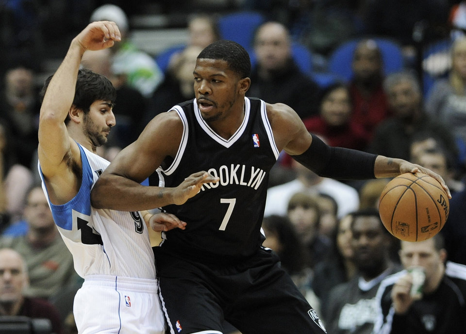 Photo - Minnesota Timberwolves' Ricky Rubio, left, of Spain, gets an elbow in the ribs by Brooklyn Nets' Joe Johnson in the first half of an NBA basketball game on Wednesday, Jan. 23, 2013, in Minneapolis. Johnson and teammate Deron Williams each scored 18 points in the Nets' 91-83 win. (AP Photo/Jim Mone)