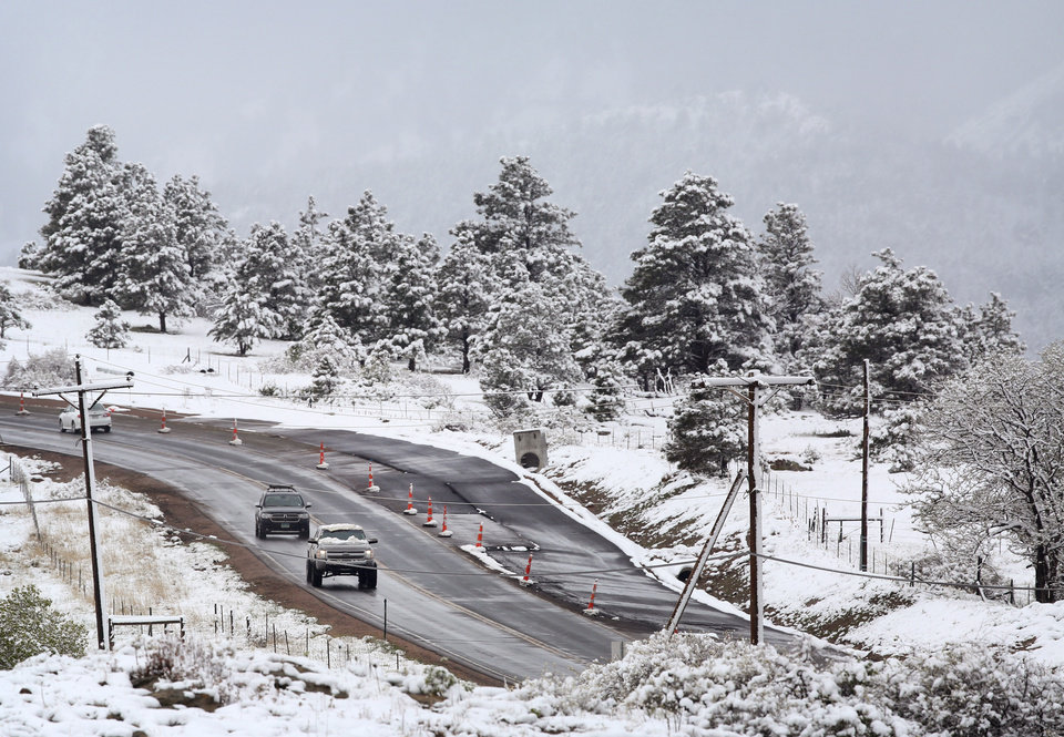 Photo - Commuters pass fresh snow from the fringe of a major spring snowstorm in the nearby mountains, in Superior, Colo., on Monday, May 12, 2014. A spring storm has brought up to 3 feet of snow to the Rockies and severe thunderstorms and tornadoes to the Midwest. In Colorado, the snow that began falling on Mother's Day caused some power outages as it weighed down newly greening trees. (AP Photo/Brennan Linsley)