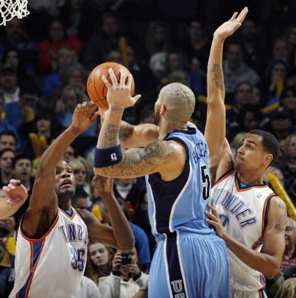 Photo - Oklahoma City's Kevin Durant (35), left, and  Thabo  Sefolosha (2) defend Carlos Boozer (5) of Utah in the first quarter during the NBA basketball game between the Oklahoma City Thunder and the Utah Jazz at the Ford Center in Oklahoma City, Thursday, December 31, 2009. Photo by Nate Billings