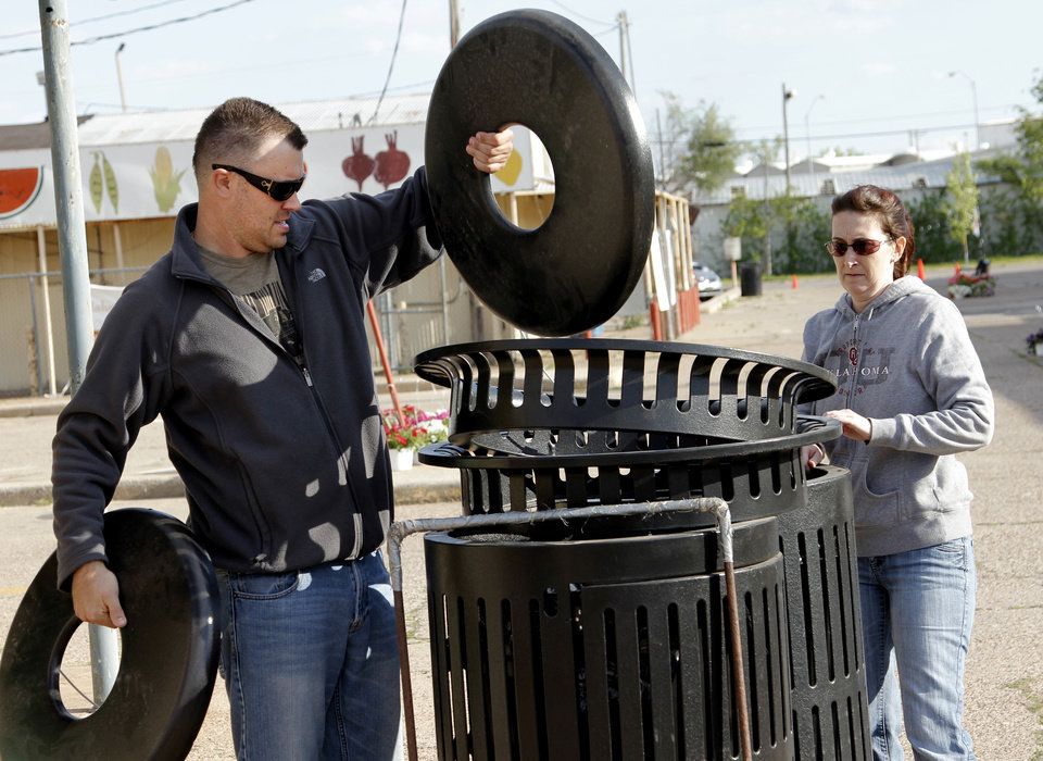 Photo - Chris Beumer and Jennifer Gates place trace receptacles  while setting up for Saturday's Better Block Party in the Farmer's Market District. Pelco Products also donated permanent directional signs for the district.  DOUG HOKE - THE OKLAHOMAN