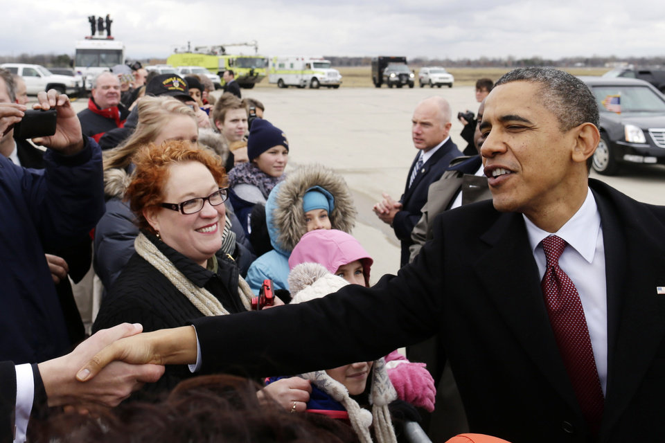 Photo - President Barack Obama greets well-wishers after stepping off Air Force One upon his arrival at  Metropolitan Wayne County Airport in Detroit, Monday, Dec. 10, 2012, before going to the Daimler Detroit Diesel plant in Redford, Mich. (AP Photo/Charles Dharapak)