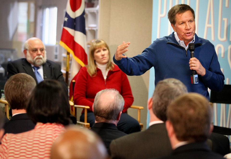 Ohio Governor John Kasich speaks to a crowd at Early Express Services  in Dayton Thursday Feb. 7, 2013 about his budget and tax plans. In the backgorund are Early Express president Cindy Woodward and Larry Dosser, president and CEO of MLPC. (AP Photo/Dayton Daily News, Jim Witmer) WKEF OUT WRGT OUT WDTN OUT LOCAL PRINT OUT