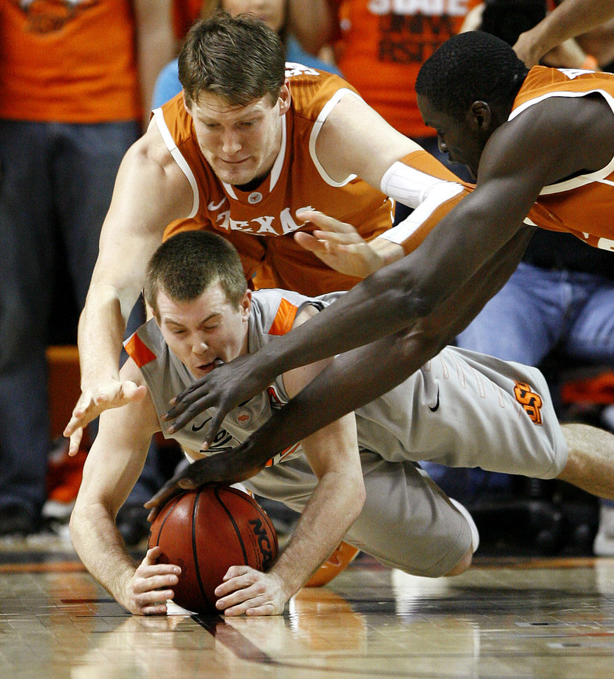 Photo - Oklahoma State's Keiton Page (12) dives for the ball between Texas' Clint Chapman (53) and Alexis Wangmene (20) during an NCAA college basketball game between Oklahoma State University (OSU) and the University of Texas (UT) at Gallagher-Iba Arena in Stillwater, Okla., Saturday, Feb. 18, 2012. Oklahoma State won 90-78. Photo by Bryan Terry, The Oklahoman