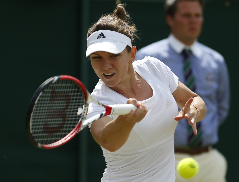 Photo - Simona Halep of Romania plays a return to Lesia Tsurenko of Ukraine during their women's singles match at the All England Lawn Tennis Championships in Wimbledon, London, Friday, June 27, 2014. (AP Photo/Alastair Grant)