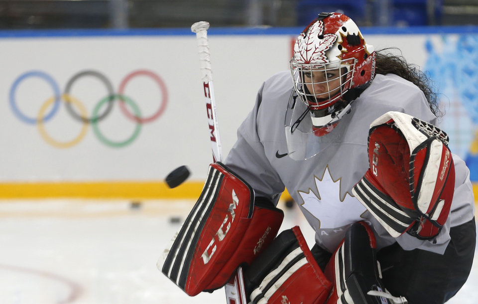 Photo - Goalkeeper of Canada's women's ice hockey team Charline Labonte eyes a puck during a practice session ahead of the 2014 Winter Olympics, Thursday, Feb. 6, 2014, in Sochi, Russia. (AP Photo/Petr David Josek)