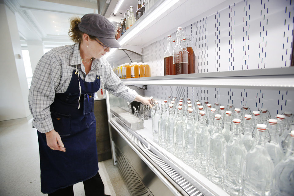 Photo - Darien Holt stocks the cooler with filtered water at Kitchen 324 in Oklahoma City.  Steve Gooch - The Oklahoman