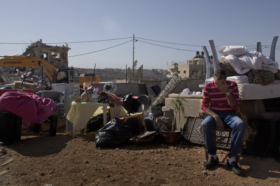 Photo - A Palestinian man sits next to his belongings while a bulldozer, background, demolishes his families house in the east Jerusalem neighborhood of Beit Hanina, Tuesday, Oct. 29, 2013. Jerusalem's municipality said the house was built illegally and that the demolition was carried out as per a court ruling. Palestinians claim that it is impossible to obtain permits. (AP Photo/Bernat Armangue)