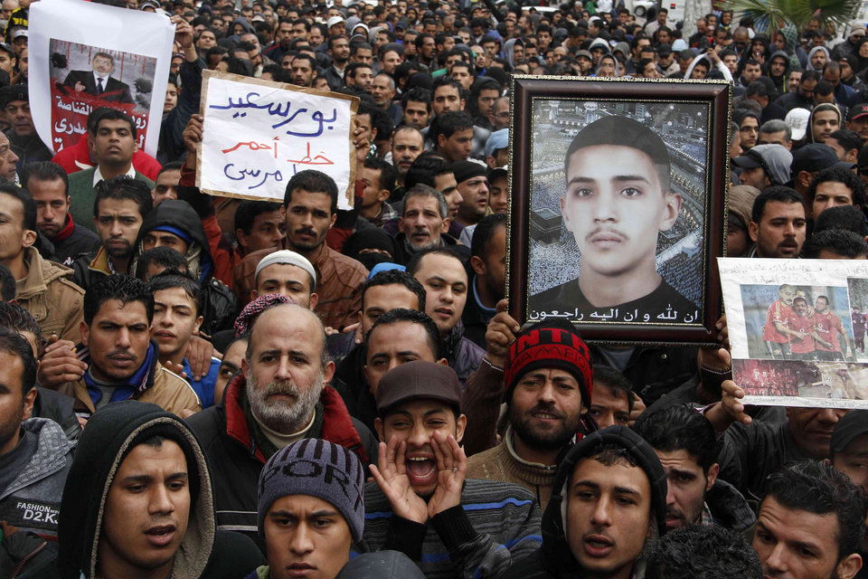 Photo - Protesters chant slogans and hold a picture of a slain young man in Port Said, Egypt, Friday, Feb. 1, 2013. Protests were held in cities around the country on Friday after a call for rallies by opponents of Islamist President Mohammed Morsi. But some cracks appeared in the ranks of the opposition as some sharply criticized its political leaders for holding their first meeting with the rival Muslim Brotherhood a day earlier. Arabic on the placard at center reads
