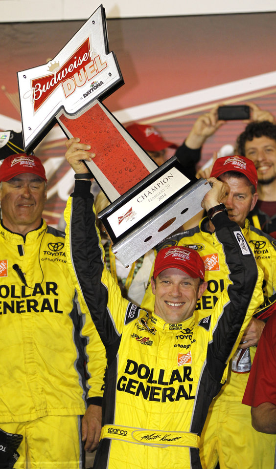 Photo - Matt Kenseth raises the trophy in Victory Lane after winning the first of two NASCAR Sprint Cup series qualifying auto races at Daytona International Speedway in Daytona Beach, Fla., Thursday, Feb. 20, 2014. (AP Photo/Terry Renna)