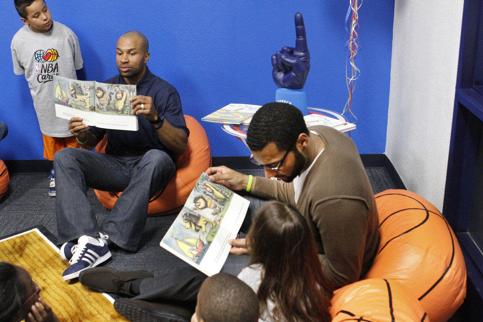 Photo - Oklahoma City Thunder's Derek Fisher, left and Lazar Hayward read to children at the opening of the NBA Cares Learn & Play Center at the City Rescue Mission on Wednesday. Photo By Steve Gooch, The Oklahoman