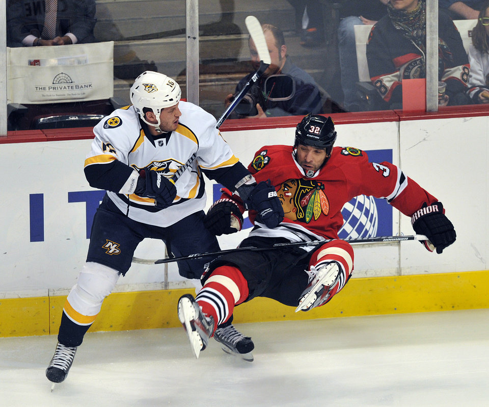 Photo - Nashville Predators' Richard Clune left, checks the Chicago Blackhawks' Michal Rozsival during the first period of an NHL hockey game Monday, April 1, 2013, in Chicago. (AP Photo/Jim Prisching)