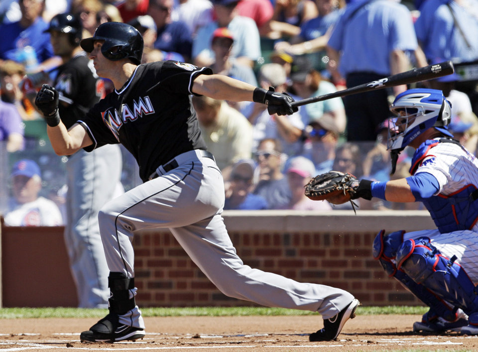 Photo - Miami Marlins' Ed Lucas hits a single against the Chicago Cubs during the first inning of a baseball game in Chicago, Friday, June 6, 2014. (AP Photo/Nam Y. Huh)