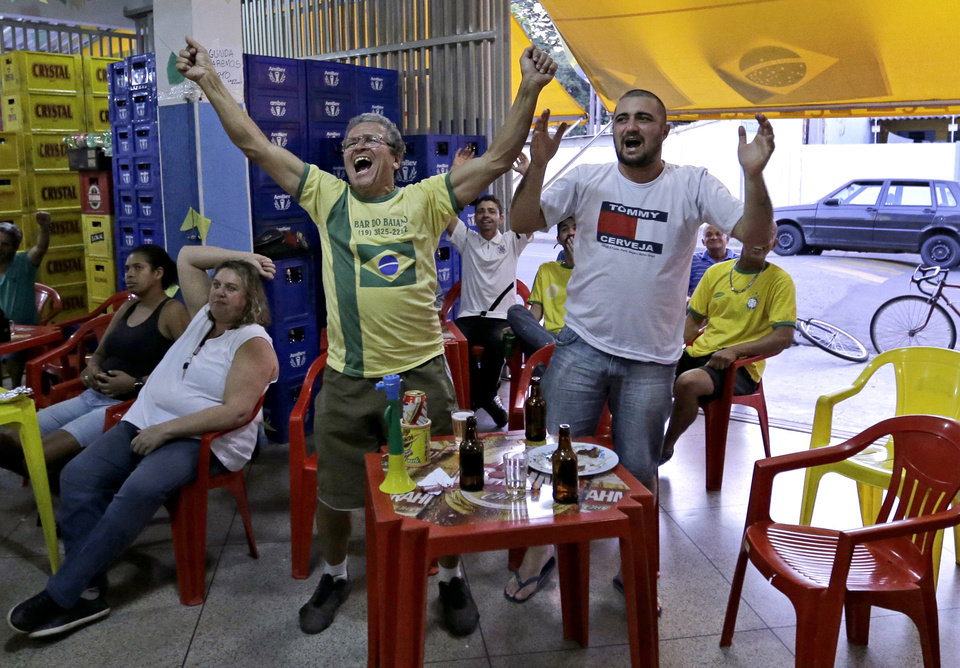 Photo - Brazil supporters cheer as they watch on the television the group A World Cup soccer match between Brazil and Mexico, at a bar in Indaiatuba, Brazil, Tuesday, June 17, 2014.(AP Photo/Shuji Kajiyama)