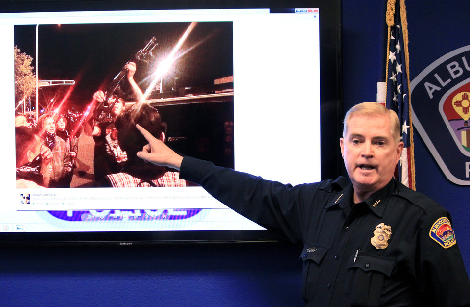 Photo - Albuquerque Police Chief Gorden Eden shows the image of a man who brought a rifle to an hours' long protest over police shootings during a news conference in Albuquerque, N.M. on Monday, March 31, 2014. Eden said the protest escalated and police were forced to use tear gas to keep what he described as a mob from hurting themselves, others and damaging property. (AP Photo/Susan Montoya Bryan)
