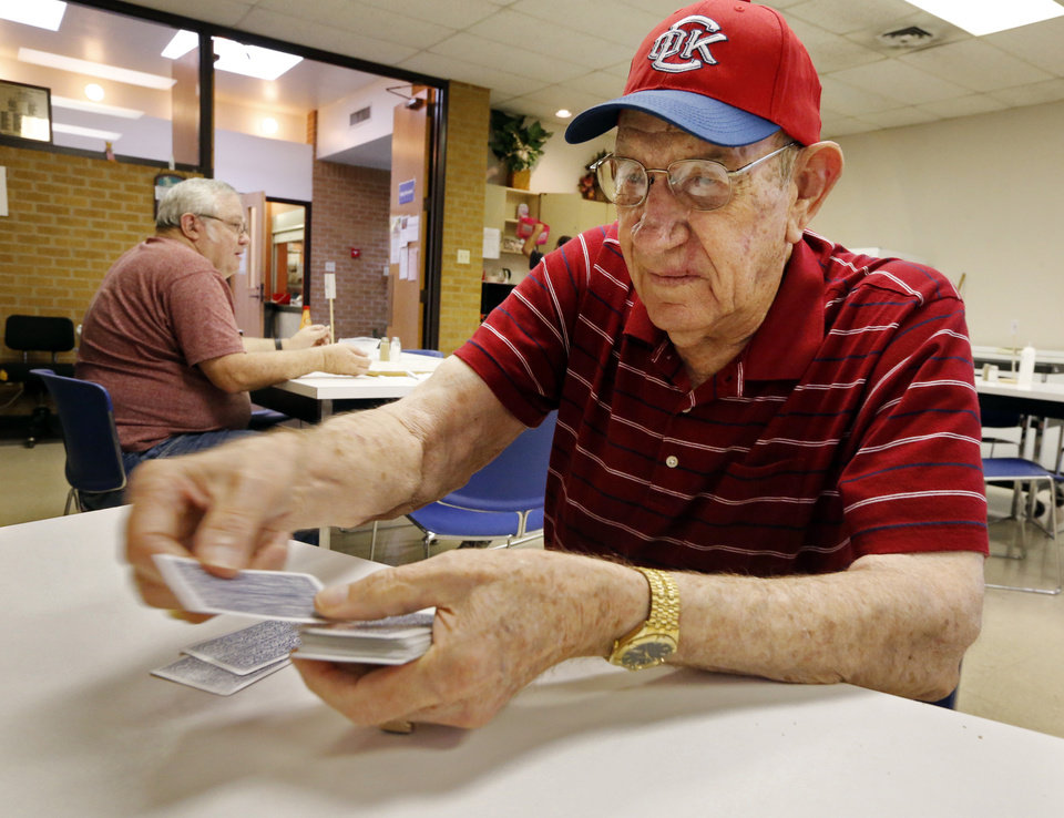 Photo -  Jim Bruehl plays cards in the basement of the old Carnegie Library building, which is the current Senior Citizens Center in Norman. Seniors have outgrown the outdated building and want a new center. [PHOTO BY STEVE SISNEY, THE OKLAHOMAN]