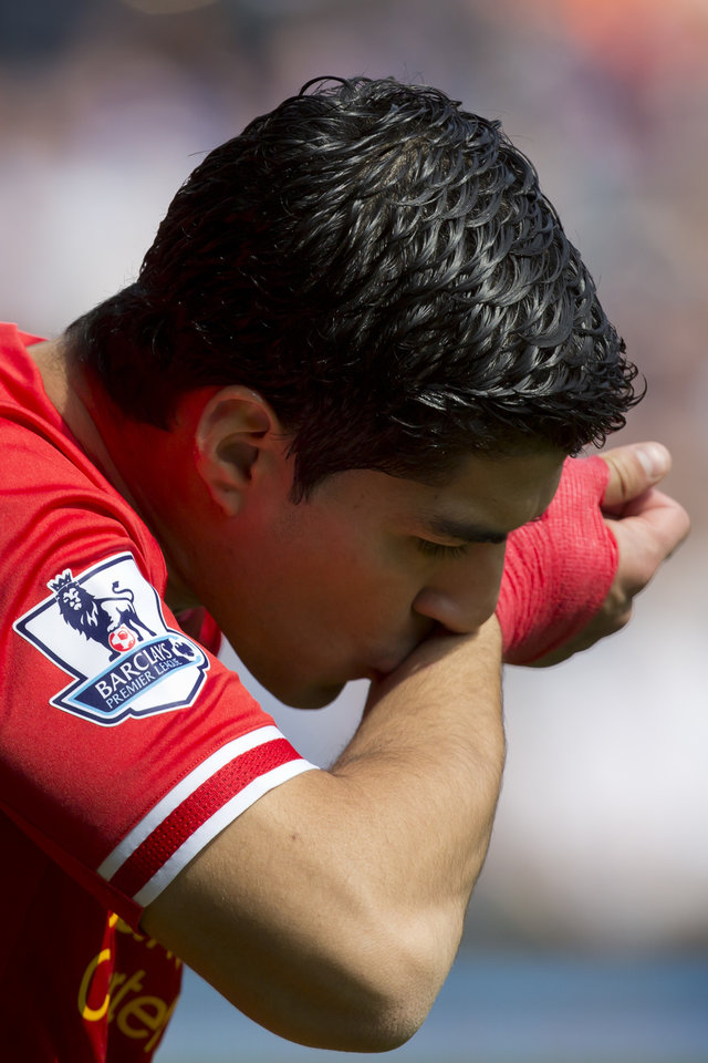 Photo - Liverpool's Luis Suarez kisses his wrist as he takes to the pitch for his team's English Premier League soccer match against Chelsea at Anfield Stadium, Liverpool, England, Sunday April 27, 2014. (AP Photo/Jon Super)