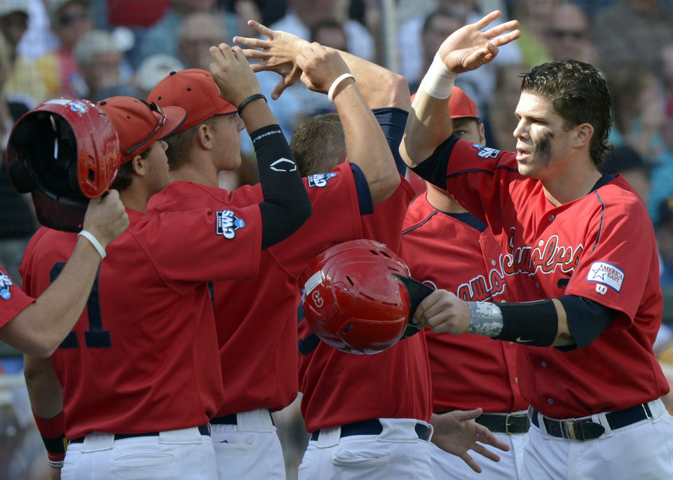 Photo -   Stony Brook's Pat Cantwell, right, celebrates with teammates after hitting a solo home run against UCLA during the third inning of an NCAA College World Series baseball game in Omaha, Neb., Friday, June 15, 2012. (AP Photo/Ted Kirk)