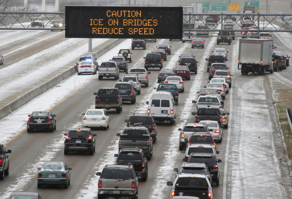 Photo - Traffic creeps along I-55 in north Jackson, Miss., Tuesday, Jan. 28, 2014 as ice and snow flurries cause difficult driving conditions. A severe winter storm is expected to hit the state bringing ice and snow to the Gulf Coast. (AP Photo/Rogelio V. Solis)