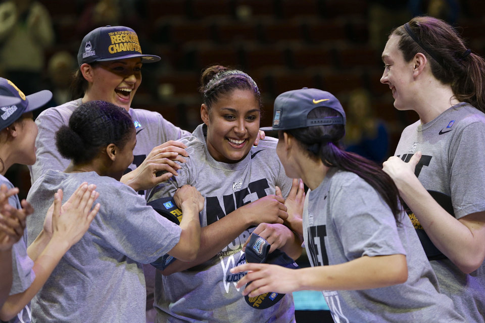 Photo - Connecticut players including Stefanie Dolson, top left, and Breanna Stewart, right, celebrate with Kaleena Mosqueda-Lewis, center, after beating Texas A&M, 69-54 in the Lincoln regional final game in the NCAA college basketball tournament in Lincoln, Neb., Monday, March 31, 2014. Connecticut advances to the final four. (AP Photo/Nati Harnik)