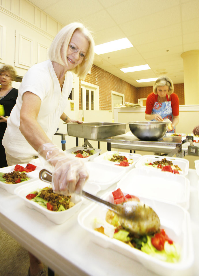 Photo - Sara Branscum prepares taco salads at Westminster Presbyterian Church in Oklahoma City to be delivered by Mobile Meals of Oklahoma County volunteers. PHOTO BY Steve Gooch, The Oklahoman
