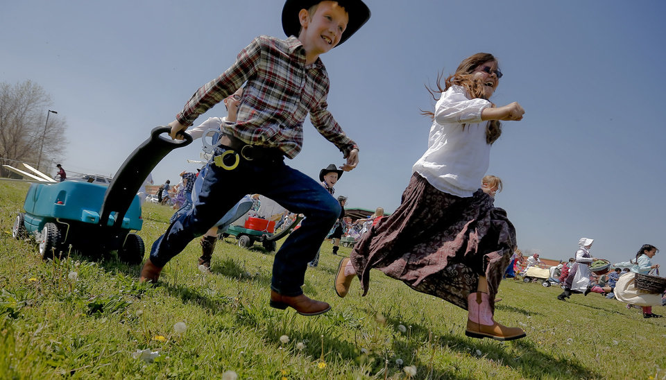 Photo - Bresson Edelen and Leslie Flores run to steak their claim of land during the Oklahoma Land Run celebration at Mustang Trails Elementary on Monday, April 22, 2013, in Mustang, Okla.   Photo by Chris Landsberger, The Oklahoman