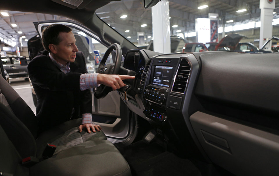 Photo -  Ford's Brandt Coultas on Wednesday points out some of the new features on the 2015 Ford F-150 XLT, which will be on display at the upcoming Oklahoma City International Auto Show at State Fair Park. Photo by Bryan Terry, The Oklahoman   BRYAN TERRY -