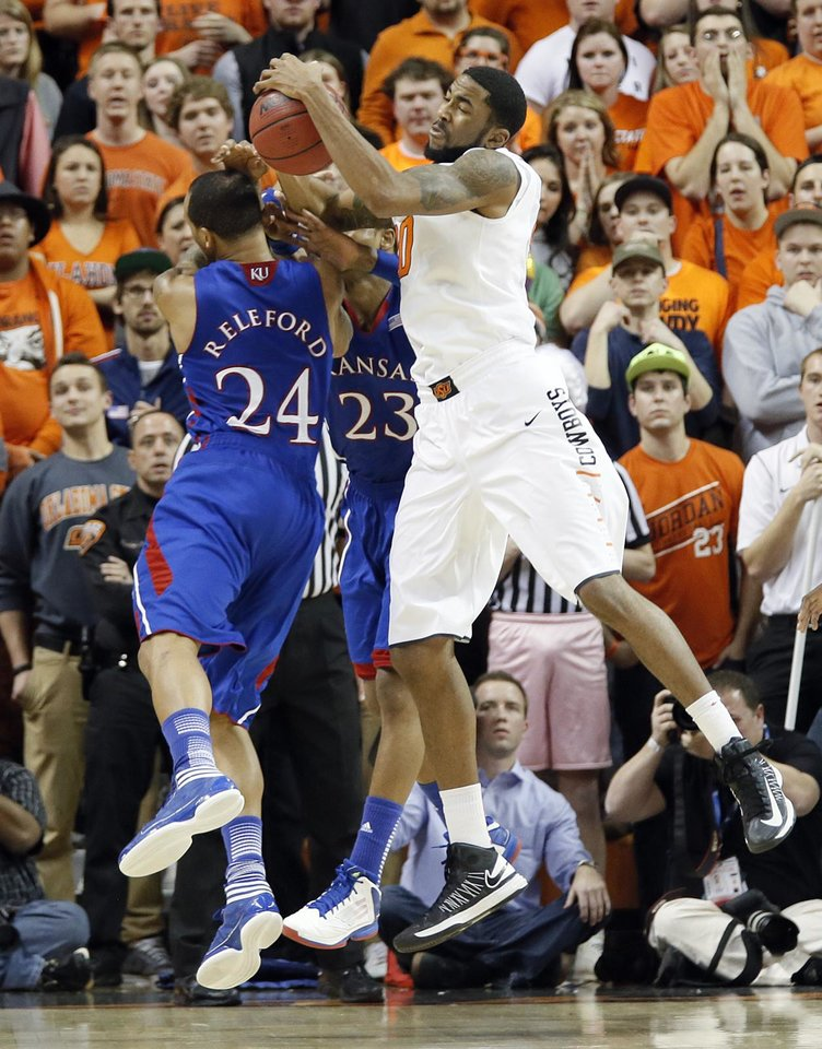 Photo - Oklahoma State 's Michael Cobbins (20) pulls in a rebound over Kansas' Travis Releford (24) during the college basketball game between the Oklahoma State University Cowboys (OSU) and the University of Kanas Jayhawks (KU) at Gallagher-Iba Arena on Wednesday, Feb. 20, 2013, in Stillwater, Okla. Photo by Chris Landsberger, The Oklahoman