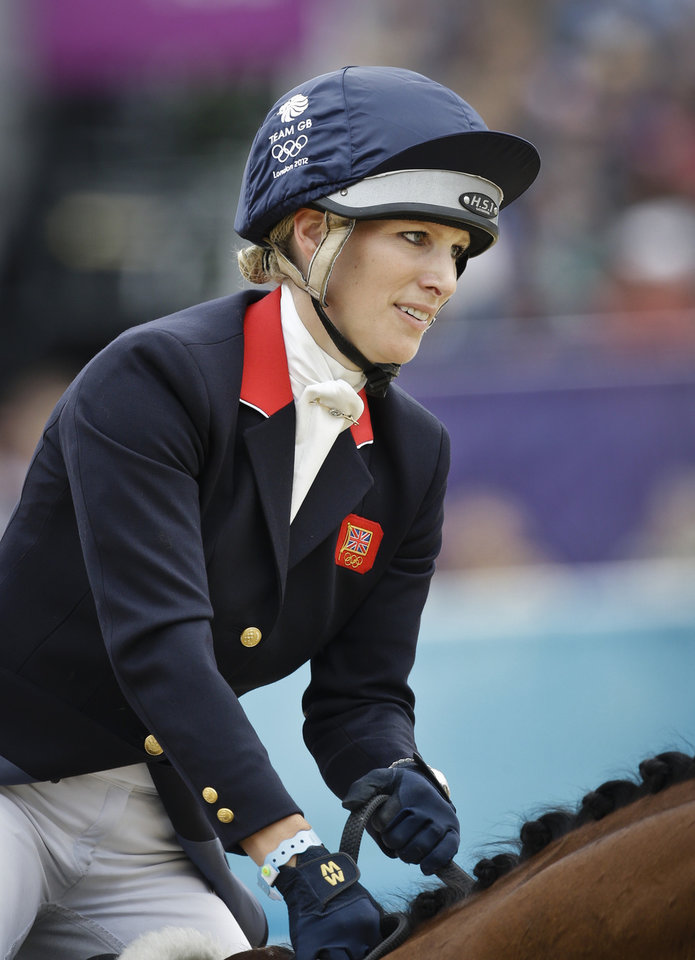 Photo - FILE - Britain's Zara Phillips and her horse High Kingdom compete in the show-jumping phase of the equestrian eventing competition at the 2012 Summer Olympics, in this file photo dated Tuesday, July 31, 2012, at Greenwich Park in London. Buckingham Palace announced Friday Jan, 17, 2014, that  Queen Elizabeth II's granddaughter Zara Phillips and husband Mike Tindall have given birth to a 7 pounds, 12 ounces (3.5 kilograms) baby girl at Gloucestershire Royal Hospital. (AP Photo/Markus Schreiber, FILE)
