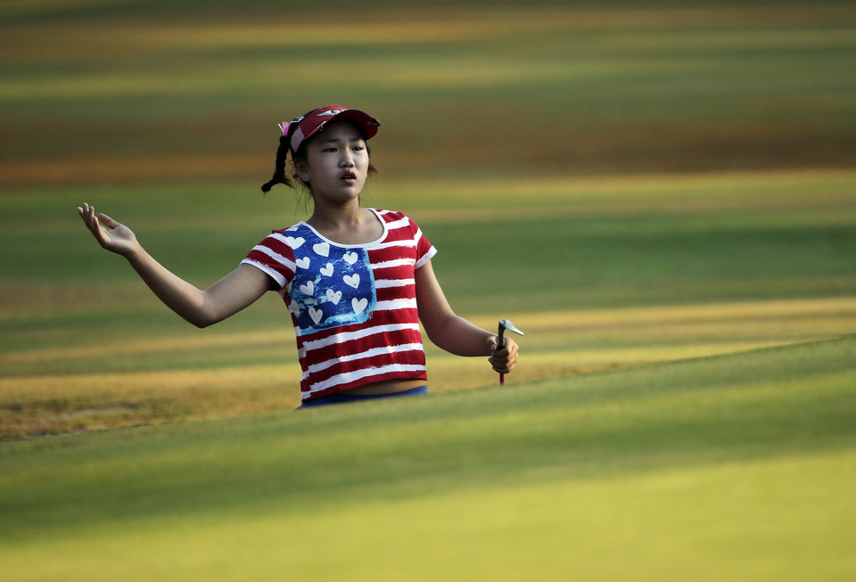 Photo - Lucy Li reacts to her shot on the 10th hole during the first round of the U.S. Women's Open golf tournament in Pinehurst, N.C., Thursday, June 19, 2014. (AP Photo/Chuck Burton)