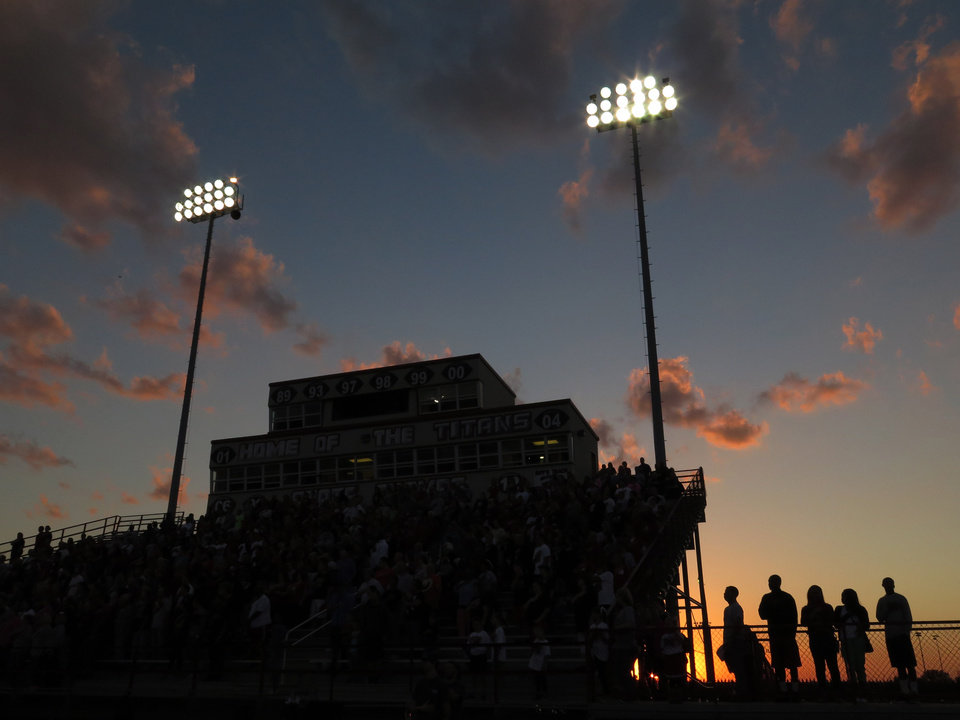 Photo - The sun sets as the National Anthem is played during the high school football game between Guthrie at Carl Albert in Midwest City, Friday, October 11, 2013.  Photo by Doug Hoke, The Oklahoman