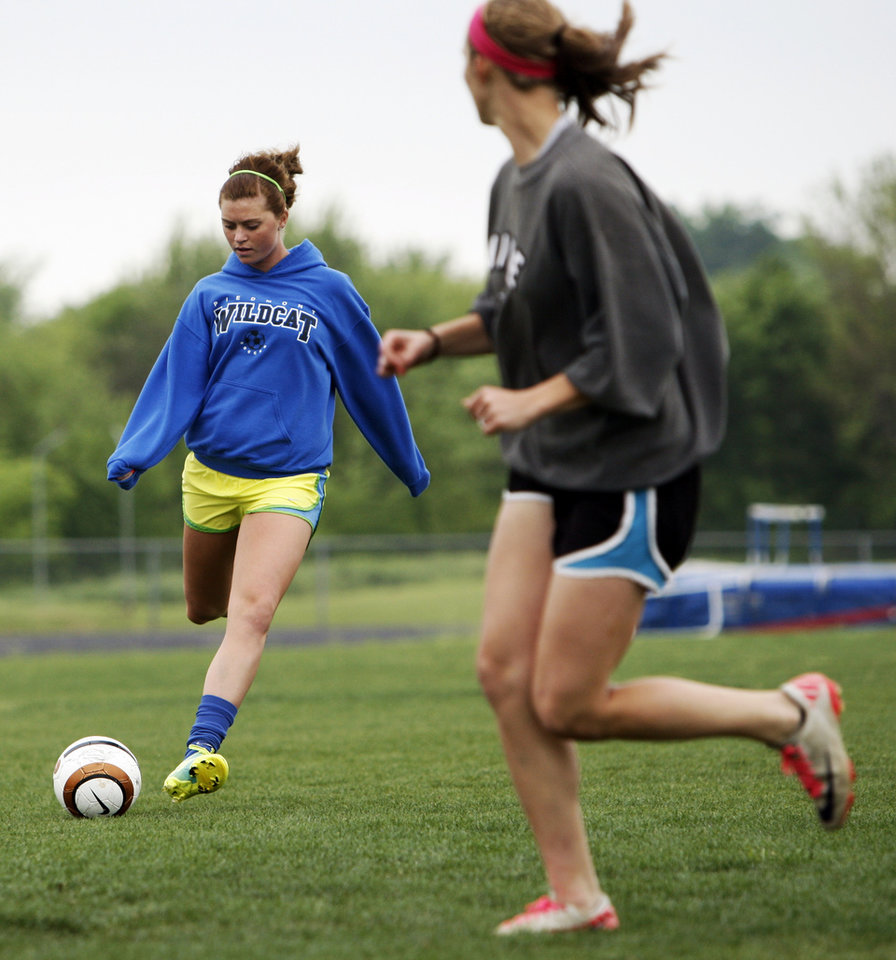 Photo - Kaylee Murphy, left, passes the ball during soccer practice at Piedmont High School in Piedmont, Okla., Wednesday, April 11, 2012. Photo by Nate Billings, The Oklahoman