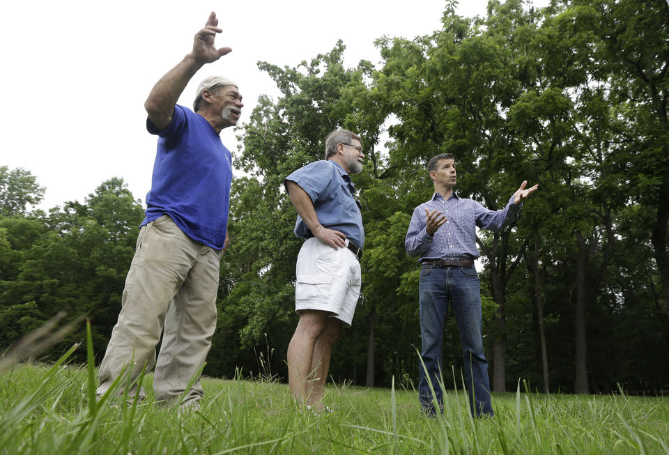 Martin Gallivan, College of William professor, right, gestures as Pamunkey Indian Jeff Brown, left, and  Randolph Turner, retired state archaeologist, center listen during a tour of a farm field overlooking the York River in  Gloucester, Va., Monday, June 17, 2013. The field is known to many in Virginia as the place where Pocahontas interceded to rescue Capt. John Smith from her powerful father, Powhatan, who ruled a vast empire in 1607  in (AP Photo/Steve Helber)
