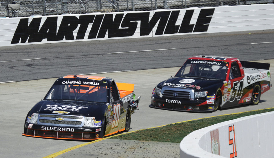 Photo - Drivers Nelson Piquet Jr. (30) and Darrell Wallace Jr. (54) make the curve in turn four during the Kroger 250 NASCAR Truck series auto race at Martinsville Speedway in Martinsville, Va., Saturday, April 6, 2013. (AP Photo/Steve Helber)