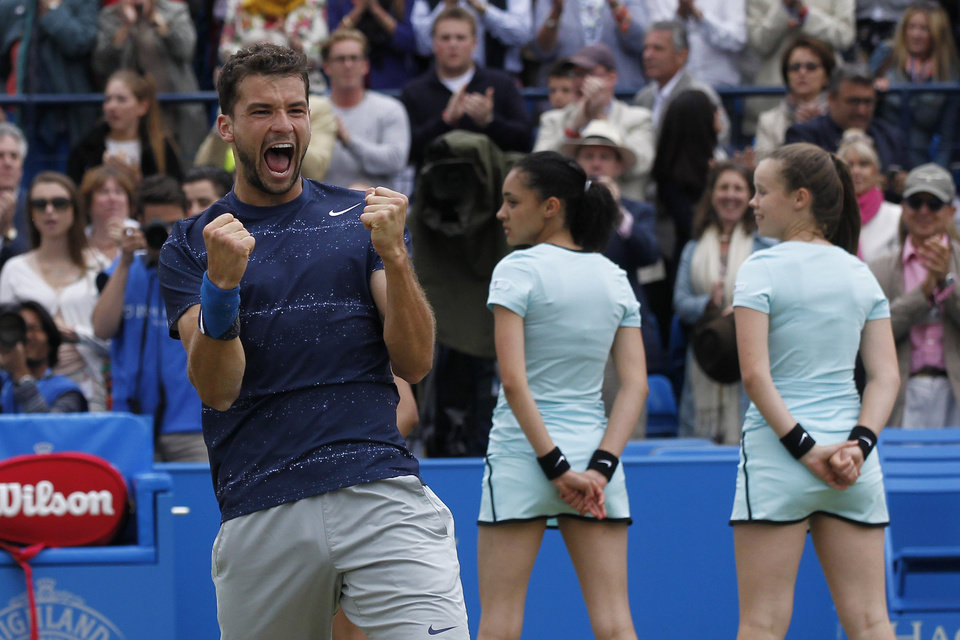 Photo - Grigor Dimitrov of Bulgaria celebrates his win against Feliciano Lopez of Spain at the end of their Queen's Club grass court championships singles final tennis match in London, Sunday, June 15, 2014. (AP Photo/Sang Tan)