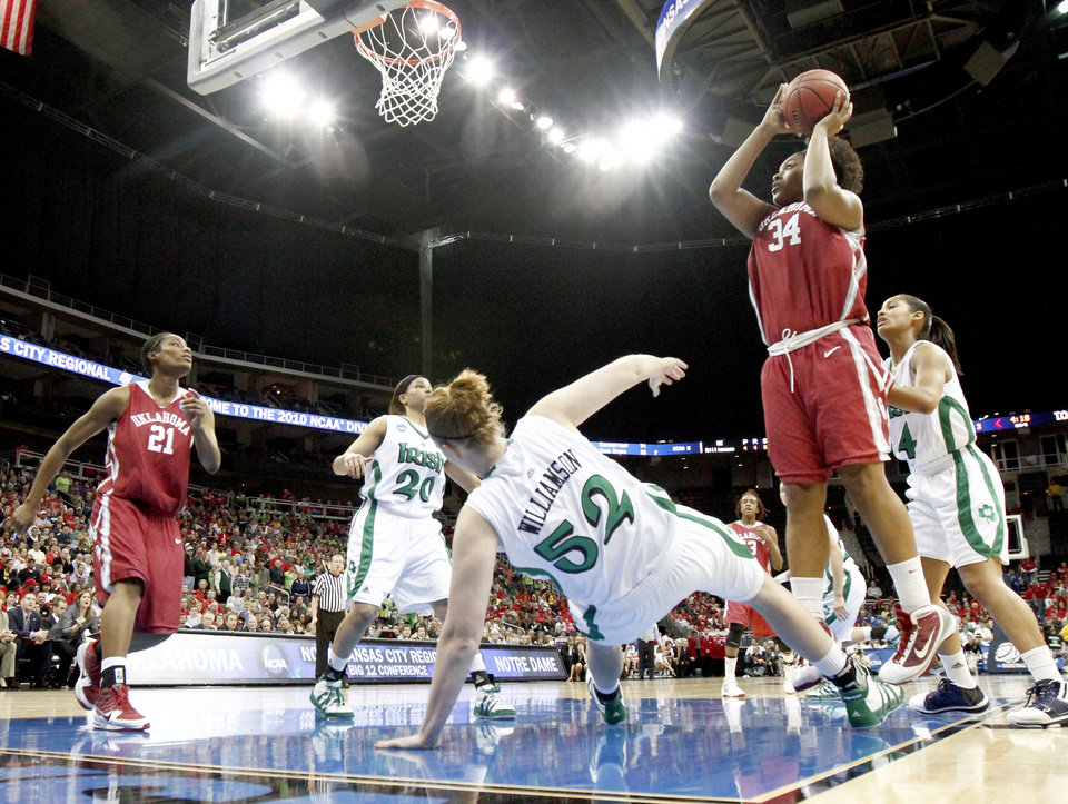 Photo - OU's Abi Olajuwon knocks down Notre Dame's Erica Williamson as she shoots the ball during the Sweet 16 round of the NCAA women's  basketball tournament in Kansas City, Mo., on Sunday, March 28, 2010. 