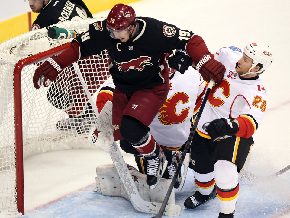 Photo - Phoenix Coyotes right winger Shane Doan (19) leaps over Calgary Flames goalie Daniel Taylor, rear, of Great Britain, while being checked by defenseman Dennis Wideman (26) in the second period of an NHL hockey game, Monday, Feb. 18, 2013, in Glendale, Ariz. (AP Photo/Paul Connors)
