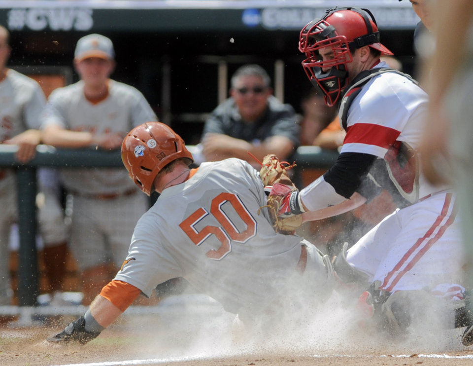 Photo - Texas'  Zane Gurwitz (50) scores at home plate against Louisville catcher Kyle Gibson, right, in the third inning of an NCAA baseball College World Series elimination game in Omaha, Neb., Monday, June 16, 2014. (AP Photo/Eric Francis)