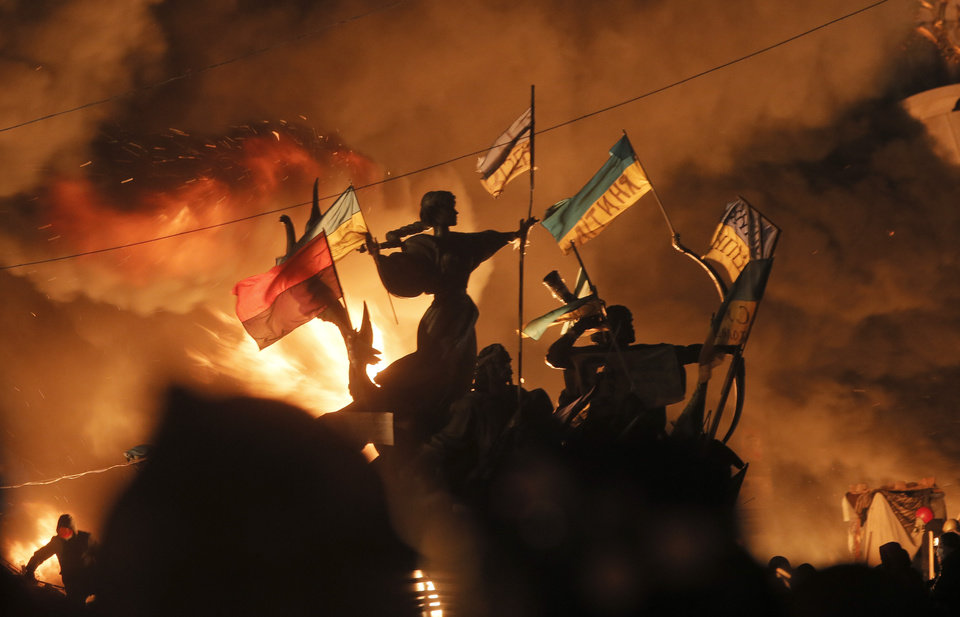 Photo - Monuments to Kiev's founders burn as anti-government protesters clash with riot police in Kiev's Independence Square, the epicenter of the country's current unrest,  Kiev, Ukraine, Tuesday, Feb. 18, 2014. Thousands of police armed with stun grenades and water cannons attacked the large opposition camp in Ukraine's capital on Tuesday that has been the center of nearly three months of anti-government protests after at least nine people were killed in street clashes. (AP Photo/Efrem Lukatsky)