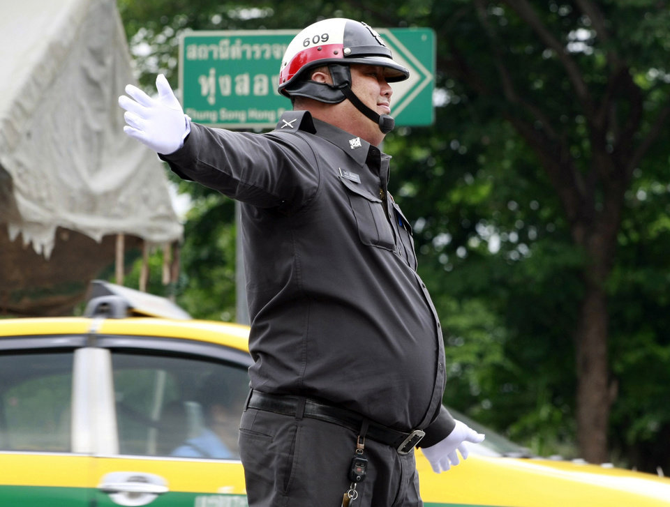 Photo - In this photo taken Thursday, July 4, 2013, an overweight traffic police officer Sgt. Wanchat Wongnothong performs his duty on a street in Bangkok, Thailand. As part of a national effort to reduce the numbers of overweight officers, Thailand has opened a 12-day boot camp to get police into shape. This week, 60 overweight officers from around the country were sent to a police training center for dawn-to-dusk exercise and lecture programs on living more healthy. (AP Photo/Apichart Weerawong)