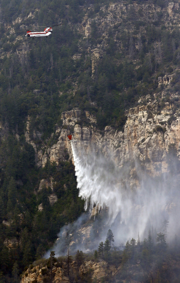Photo - A Heavy Type-1 Vertol Helictoper dumps 2,800 gallons of water onto the Slide Fire as it burns up Oak Creek Canyon on Friday, May 23, 2014, near Flagstaff, Ariz.  The fire has burned approximately 7,500 acres and is five percent contained. (AP Photo/Ross D. Franklin)