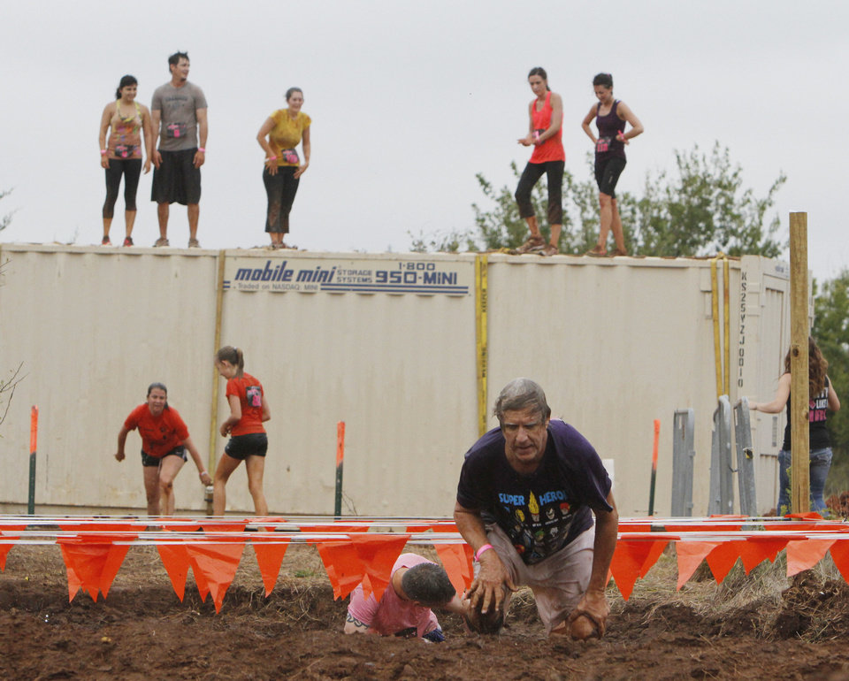 Participants negotiate the final obstacle of the Juggernaut mud run at Edmond's J.L. Mitch Park. The event raised money for Susan G. Komen for the Cure. PHOTO BY PAUL HELLSTERN, THE OKLAHOMAN <strong>PAUL HELLSTERN</strong>