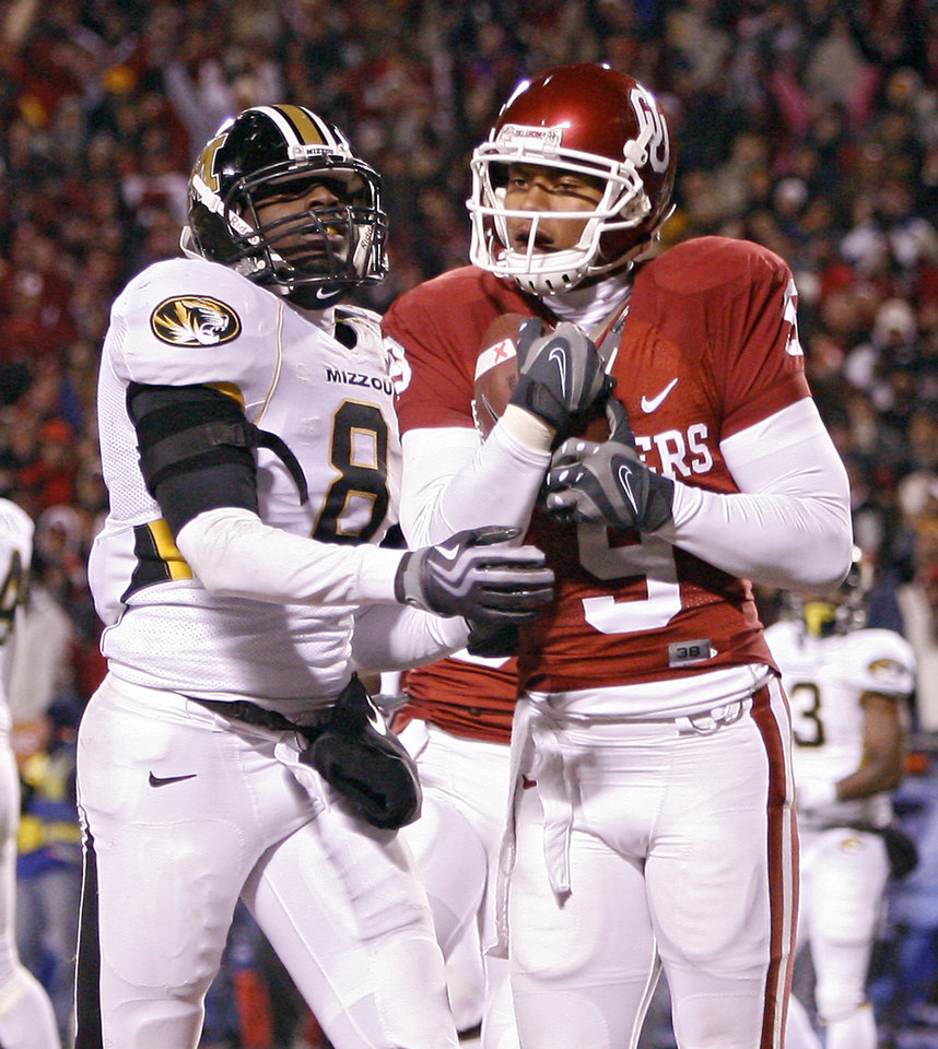Photo - Oklahoma's Juaquin Iglesias (9) makes a touchdown reception in front of Missouri's Justin Garrett (8) during the first half of the Big 12 Championship college football game between the University of Oklahoma Sooners (OU) and the University of Missouri Tigers (MU) on Saturday, Dec. 6, 2008, at Arrowhead Stadium in Kansas City, Mo. 