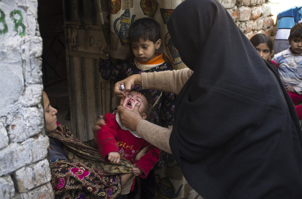 Photo - A Pakistani female polio worker administers polio drops to an infant in Christian colony situated in the slums of Islamabad, Pakistan on  Wednesday, Dec. 19, 2012 in Islamabad, Pakistan. Gunmen shot dead a woman working on U.N.-backed polio vaccination efforts and her driver in northwestern Pakistan, officials said, just a day after similar attacks across the country killed several female polio workers. (AP Photo/B.K. Bangash)
