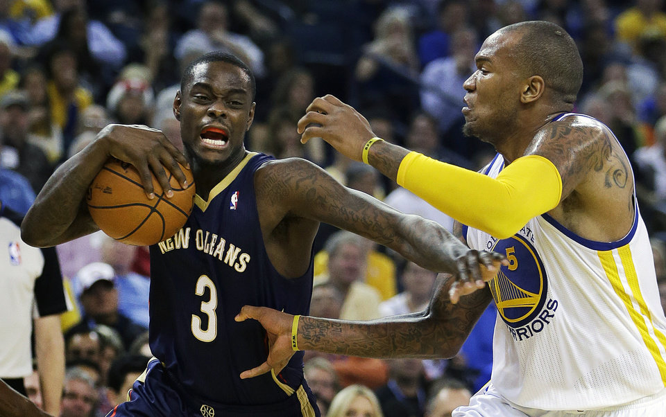 Photo - New Orleans Pelicans' Anthony Morrow (3) drives the ball against Golden State Warriors' Marreese Speights, right, during the first half of an NBA basketball game Tuesday, Dec. 17, 2013, in Oakland, Calif. (AP Photo/Ben Margot)