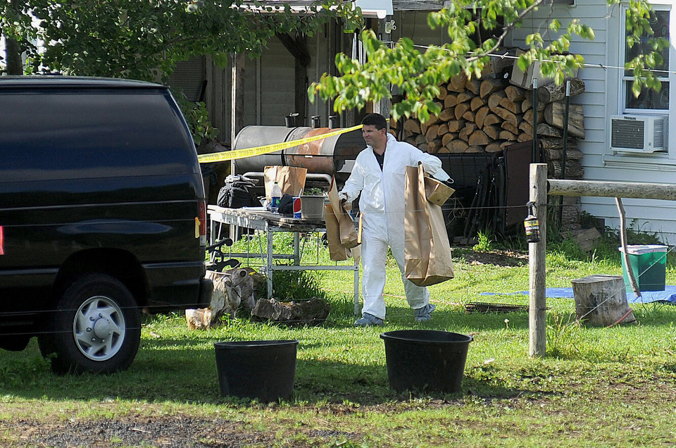 Photo - A New York State Police crime scene investigator carries evidence to a van Sunday, Aug. 17, 2014, at the home of suspected kidnappers Stephen Howells II and Nicole F. Vaisey, in Hermon, NY. The father of two Amish girls abducted in northern New York last week said he feels sorry for the two people authorities say kidnapped and sexually abused his daughters. (AP Photo/Melanie Kimbler-Lago, Watertown Daily Times)