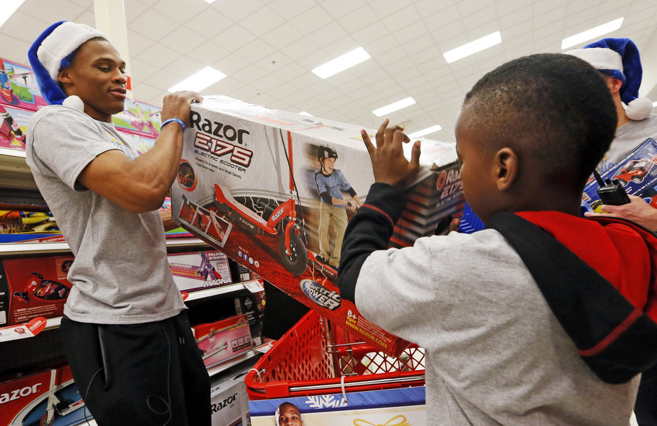 Photo - CHILD / CHILDREN / KIDS / NBA BASKETBALL / CHARITY: Russell Westbrook of the Oklahoma City Thunder helps Keylan Sanders, 8, load a scooter into a shopping cart during the Oklahoma City Thunder's annual Holiday Assist shopping spree at Target, 13924 N Pennsylvania, in Oklahoma City, Monday, Dec. 10, 2012. The ten families who participated in this year's shopping spree are from Sunbeam Family Services' Grandparents Raising Grandchildren program. Photo by Nate Billings, The Oklahoman