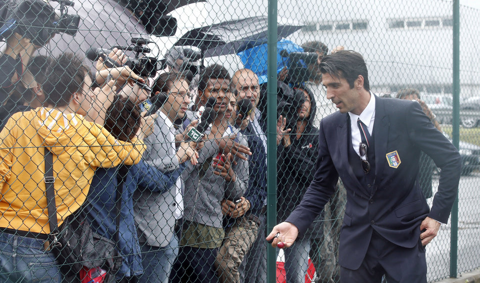Photo - Italy goalkeeper Gianluigi Buffon talks to reporters upon his arrival with his teammates at Malpensa airport after landing from Brazil, in Milan, Italy, Thursday, June 26, 2014. Italy was disqualified from the World Cup after loosing to Uruguay in their group stage round.  (AP Photo/Luca Bruno)