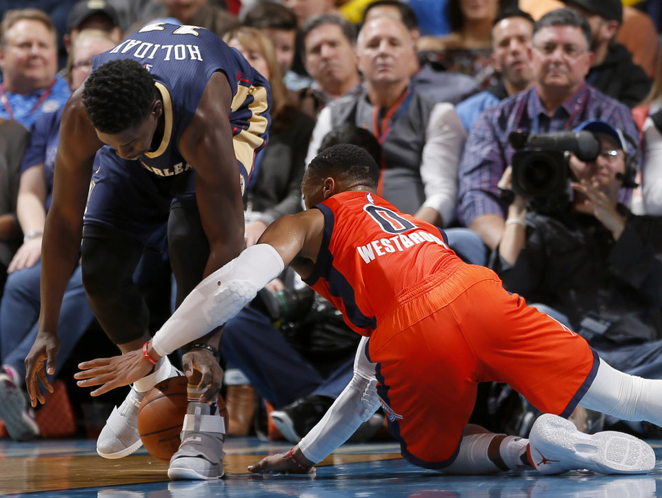 Photo - Oklahoma City's Russell Westbrook (0) scrambles for the ball from New Orleans' Jrue Holiday (11) during the NBA game between the Oklahoma City Thunder and the New Orleans Pelicans at the Chesapeake Energy Arena,  Sunday, Dec. 4, 2016. Photo by Sarah Phipps, The Oklahoman